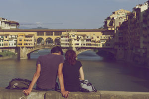 couple sitting by water in the city
