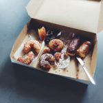 partially eaten donuts in a box
