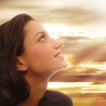 Woman looks towards heaven with joyful expression