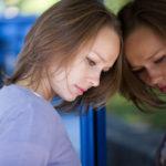 Sad woman leans against mirror