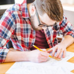 hardworking man drawing blueprints