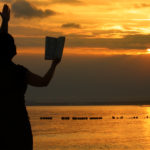 Woman stands praying from Bible at sunset