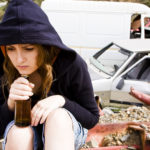 sad young woman drinking in scrapyard